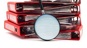 red binders and magnifying glass